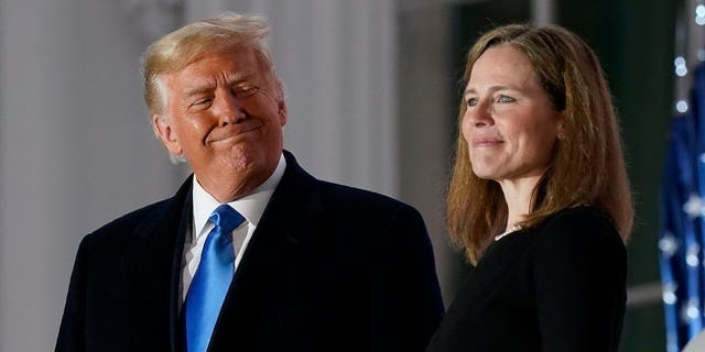 President Donald Trump and Amy Coney Barrett stand on the Blue Room Balcony after Supreme Court Justice Clarence Thomas administered the Constitutional Oath to her on the South Lawn of the White House White House in Washington, Oct. 26, 2020. (AP Photo/Patrick Semansky)