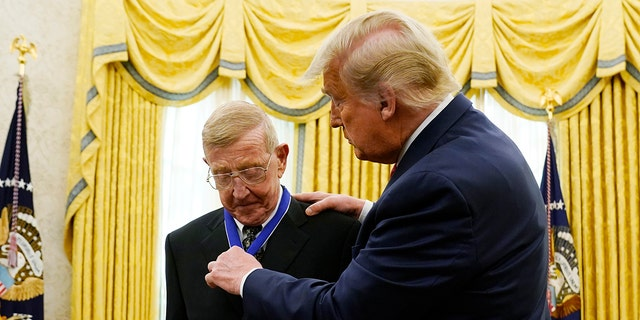 President Donald Trump awards the medal of Freedom, the highest civilian honor, to former college football coach Lou Holtz at the White House, Thursday, Dec. 3, 2020, in Washington. Holtz had a storied 34-year coaching career that included winning the 1988 national title at the University of Notre Dame. (AP Photo/Evan Vucci)
