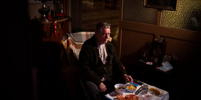 """Álvaro Puig Moreno watches television while eating a his Christmas Eve dinner at his home in Barcelona, Spain, 목요일, 12 월. 24, 2020. """"The solitude gets to me these days, I often feel depressed,"""" Puig said. """"These holidays, instead of making me happy, make me sad. I hate them. Most of family has died, I am one of the last ones left. I will spend Christmas at home alone because I don't have anyone to spend them with."""""""
