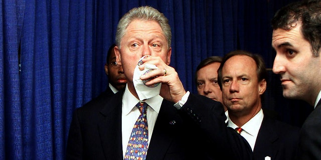 US President Bill Clinton (sinistra) takes a last sip of his Diet Coke with aide Doug Band (destra) before addressing a Democratic National Committee luncheon July 30, 2000, a Chicago. (TIM SLOAN/AFP via Getty Images)