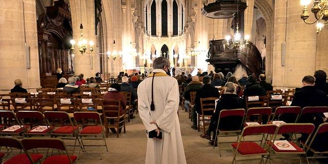 Faithful attend Christmas vespers at the Saint Germain l'Auxerrois church in Paris, Thursday, Dec. 24, 2020, in Paris. (Associated Press)