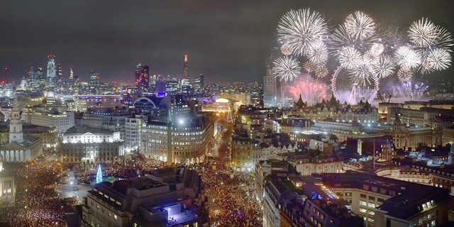 Cityscape of London at midnight on New Years eve. ThTrafalgar Square is traditionally where Londoners gather to celebrate the New Year and watch the distant fireworks along the River Thames