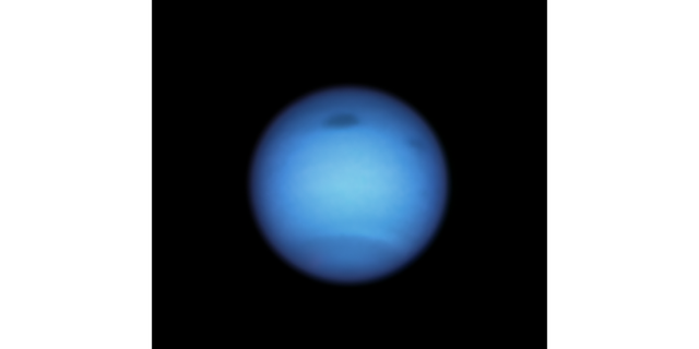 This Hubble Space Telescope snapshot of the dynamic blue-green planet Neptune reveals a monstrous dark storm (top center) and the emergence of a smaller dark spot nearby (top right). (NASA, ESA, STScI, M.H. Wong/University of California, Berkeley and L.A. Sromovsky and P.M. Fry/University of Wisconsin-Madison))