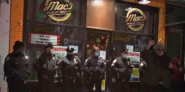 Protesters gather outside Mac's Public House on Staten Island Wednesday night to voice anger against the arrest of the bar's co-owner for allegedly refusing to obey coronavirus restrictions.
