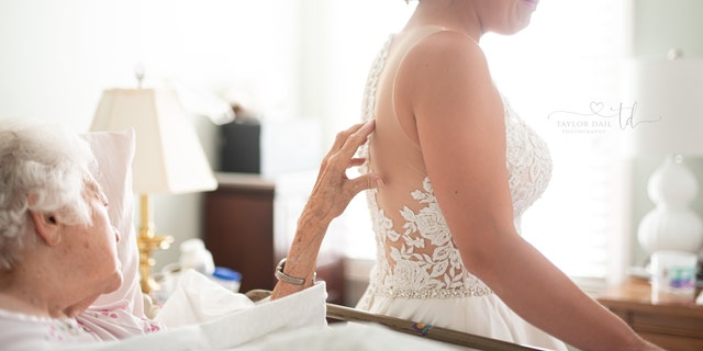 The bride cried as her grandmother touched the detailing on her back.