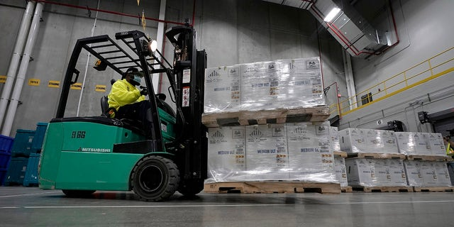 Boxes containing the Pfizer-BioNTech COVID-19 vaccine are moved to the loading dock for shipping at the Pfizer Global Supply Kalamazoo manufacturing plant in Portage, Mich., Sunday, Dec. 13, 2020.