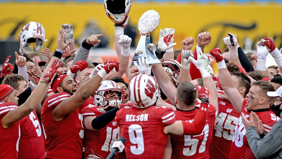 Wisconsin Badgers QB fumbles bowl-game trophy, smashing it on floor, videos show