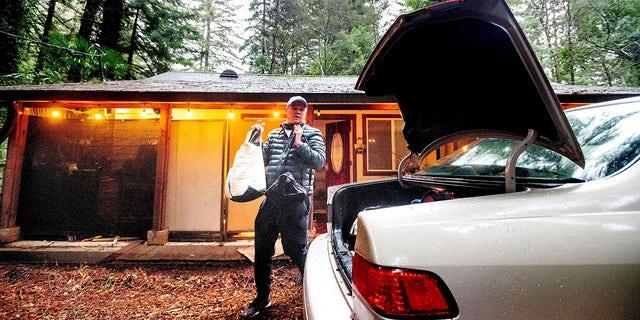 Charles Bogray evacuates from his Boulder Creek home near the CZU Lightning Complex Fire burn zone in Santa Cruz County, Calif., on Tuesday, Jan. 26, 2021. (AP Photo/Noah Berger)