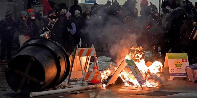 Trash burns as people take part in a protest against police brutality, late Sunday, Jan. 24, 2021, in downtown Tacoma, Wash., south of Seattle. The protest came a day after at least two people were injured when a Tacoma Police officer responding to a report of a street race drove his car through a crowd of pedestrians that had gathered around him. Several people were knocked to the ground and at least one person was run over. (AP Photo/Ted S. Warren)