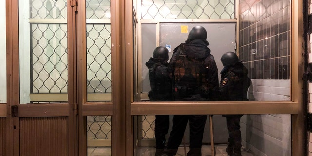 Police stand in front of a door of the apartment building where Oleg Navalny, brother of jailed opposition leader Alexei Navalny lives in Moscow, 러시아, 수요일, 1 월. 27, 2021. Police are searching the Moscow apartment of jailed Russian opposition leader Alexei Navalny, another apartment where his wife is living and two offices of his anti-corruption organization. Navalny's aides reported the Wednesday raids on social media. (AP Photo/Mstyslav Chernov)