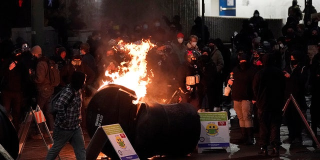 A trash can burns as people take part in a protest against police brutality, late Sunday, Jan. 24, 2021, in downtown Tacoma, Wash. (Associated Press)