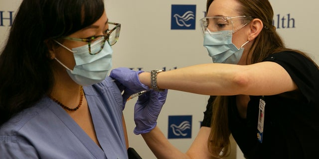 Registered nurse Carol Eickmeyer, left, gets the first vaccination for the coronavirus from RN Cassandra Antosz at Sacred Heart RiverBend Hospital in Springfield, Ore., on Dec. 21, 2020. (Associated Press)