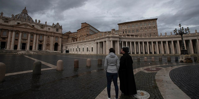 Two people stand in an empty St. Peter's Square at the Vatican as Pope Francis recites the Angelus noon prayer in his studio Friday, Jan. 1, 2021. (AP Photo/Alessandra Tarantino)