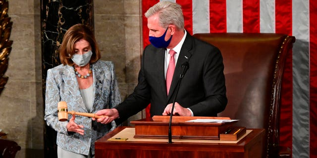 Speaker of the House Nancy Pelosi is handed the Speaker's gavel by House Minority Leader Kevin McCarthy, R-Calif., on the opening day of the 117th Congress on Capitol Hill in Washington, Sunday, Jan. 3, 2021.