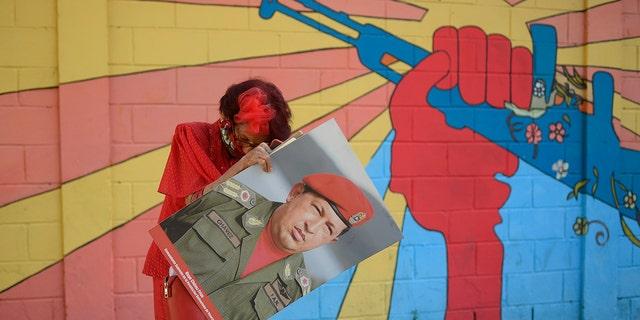 """एक सरकारी समर्थक के रूप में जाना जाता है """"लिटिल रेड राइडिंग हुड,"""" या लिटिल रेड राइडिंग हूड, स्वर्गीय वेनेजुएला के राष्ट्रपति ह्यूगो शावेज की एक तस्वीर रखता है क्योंकि वह नेशनल असेंबली के पास प्लाजा बोलिवर में अपने पर्स में कुछ ढूंढता है, जहां नव निर्वाचित राष्ट्रीय विधानसभा सांसदों को शपथ दिलाई जाएगी और वर्ष का पहला सत्र आयोजित किया जाएगा। काराकास, वेनेजुएला, मंगलवार, 5 जनवरी, 2021। (एपी फोटो / माटीस डेलाक्रोइक्स)"""