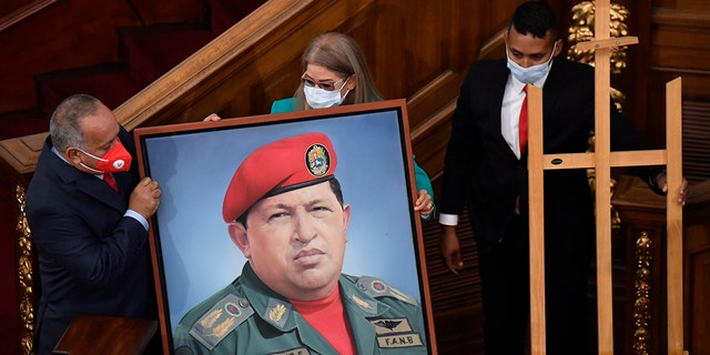First lady Cilia Flores, center, and Diosdado Cabello, president of the Constitutional Assembly, carry a portrait of late Venezuelan President Hugo Chavez into the chamber of the National Assembly, as the ruling socialist party prepares to assume the leadership of Congress in Caracas, Venezuela, Tuesday, Jan. 5, 2021. Ruling party allies swept legislative elections last month boycotted by the opposition. (AP Photo/Matias Delacroix)