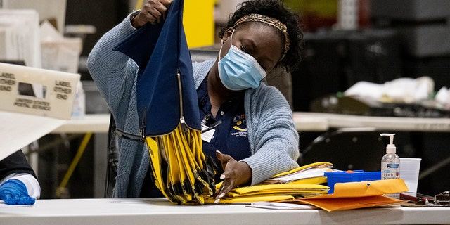 An election worker at the Fulton County Georgia elections warehouse empties a bag following the Senate runoff election in Atlanta on Tuesday, Jan. 5, 2021. (AP Photo/Ben Gray)