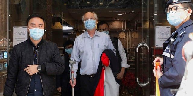 अमेरिकी मानवाधिकार वकील जॉन क्लेन्सी, केंद्र, हांगकांग में बुधवार, 6 जनवरी, 2021 को पुलिस द्वारा गिरफ्तार किया गया है। (एसोसिएटेड प्रेस)