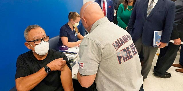 In this Jan. 4, 2021, file photo, Florida Gov. Ron DeSantis, right rear, watches as Carlos Dennis, left, 65, rolls up his sleeve so that Miami-Dade County Fire Rescue paramedic, Capt. Javier Crespo, can administer a COVID-19 vaccine shot at Jackson Memorial Hospital in Miami.