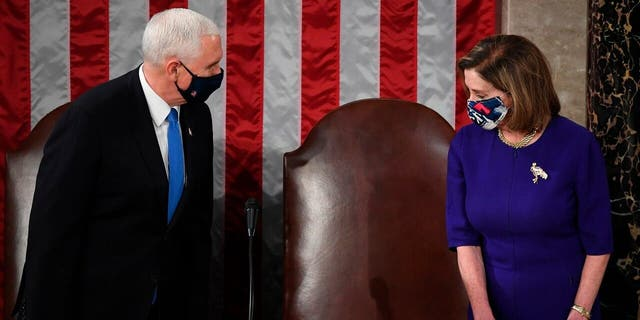Speaker of the House Nancy Pelosi, D-Calif., and Vice President Mike Pence talk before a joint session of the House and Senate convenes to count the Electoral College votes cast in November's election, at the Capitol in Washington, Wednesday, Jan. 6, 2021. (Saul Loeb/Pool via AP)