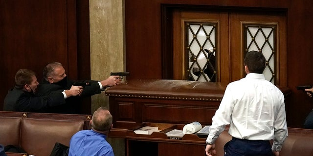 Police with guns drawn watch as protesters try to break into the House Chamber at the U.S. Capitol on Wednesday in Washington. (AP Photo/J. Scott Applewhite)