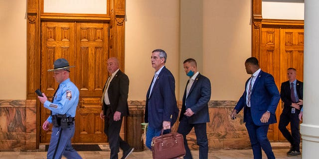 Lead by a Georgia State Trooper, Georgia Secretary of State Brad Raffensperger, center, exits the Georgia State Capitol building after hearing reports of threats, Jan. 6, in Atlanta.