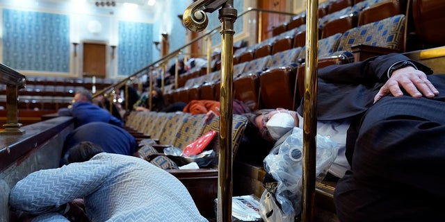 People shelter in the House gallery as protesters try to break into the House Chamber at the U.S. Capitol on Wednesday. (AP Photo/Andrew Harnik)