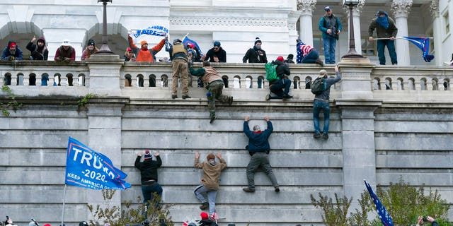 Supporters of President Trump climb the west wall of the the U.S. Capitol on Wednesday, Jan. 6, 2021, in Washington.<br>