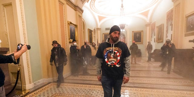 Smoke fills the walkway outside the Senate Chamber as supporters of President Donald Trump are confronted by U.S. Capitol Police officers inside the Capitol, Jan. 6, in Washington. (AP Photo/Manuel Balce Ceneta)