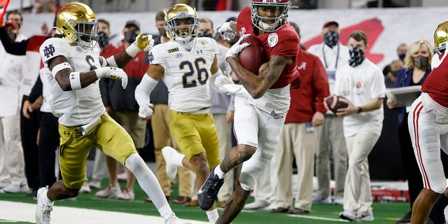 Alabama wide receiver DeVonta Smith (6) gets past Notre Dame linebacker Jeremiah Owusu-Koramoah (6) and cornerback Clarence Lewis (26) on his way to the end zone for a touchdown in the first half of the Rose Bowl NCAA college football game in Arlington, Texas, in this Friday, Jan. 1, 2021, file photo. (AP Photo/Michael Ainsworth, File)