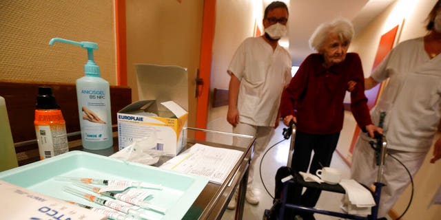 A resident is led to get the Pfizer-BioNTech COVID-19 vaccine at the Bois Fleuris nursing home in Strasbourg in eastern France, Jan. 6, 2021. (Associated Press)