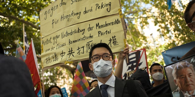 Hong Kong activist Nathan Law, sentrum, takes part in a protest during the visit of Chinese Foreign Minister Wang Yi in Berlin, Duitsland, op Sept.. 1, 2020.  (AP Photo/Markus Schreiber, lêer)