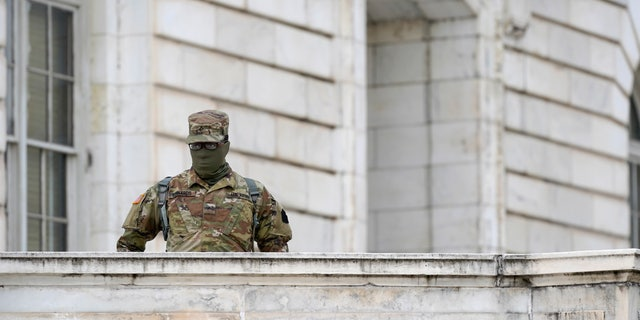 A member of the military stands guard outside Russell Senate Office Building on Capitol Hill in Washington, Friday, Jan. 8, 2021, in response to supporters of President Donald Trump who stormed the U.S. Capitol.