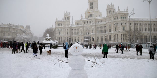 People walk past the Cibeles monument, left, in front of the City Hall during a heavy snowfall in downtown Madrid, Spain, Saturday, Jan. 9, 2021. A persistent blizzard has blanketed large parts of Spain with 50-year record levels of snow, halting traffic and leaving thousands trapped in cars or in train stations and airports that suspended all services as the snow kept falling on Saturday. (AP Photo/Andrea Comas)