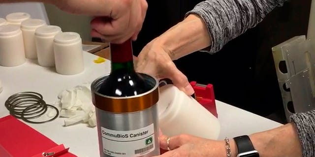 Researchers from Space Cargo Unlimited prepare bottles of French red wine to be flown from Wallops Island, VA, to the International Space Station on Nov. 2, 2019. (Space Cargo Unlimited via AP)