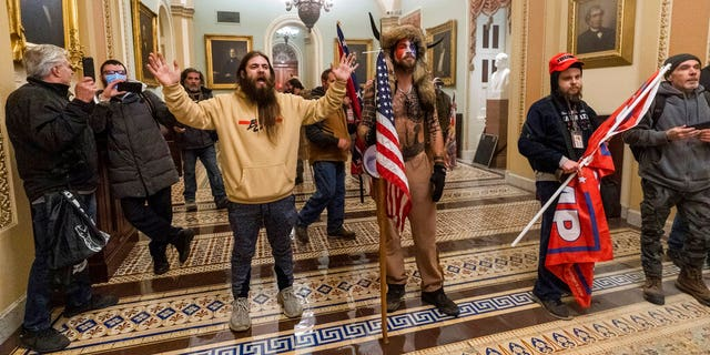 Supporters of President Donald Trump are confronted by U.S. Capitol Police officers outside the Senate Chamber inside the Capitol in Washington on Jan. 6, 2021. Jacob Anthony Chansley, the Arizona man with the painted face and wearing a horned, fur hat, was taken into custody Saturday. (AP Photo/Manuel Balce Ceneta, file)
