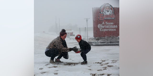 Heather makes a snowball and hands it to her son, Weston, 5, to build a snowman at Santa's Wonderland on Highway 6 Domenica, Jan. 10, 2021, in College Station, Texas. The family of five drove up from Waller to find snow. (Yi-Chin Lee/Houston Chronicle via AP)