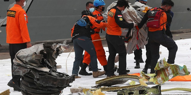 Rescuers carry debris found in the waters around the location where Sriwijaya Air passenger jet crashed at Tanjung Priok Port in Jakarta, Indonesia, Monday, Jan. 11, 2021.  (AP Photo/Achmad Ibrahim)