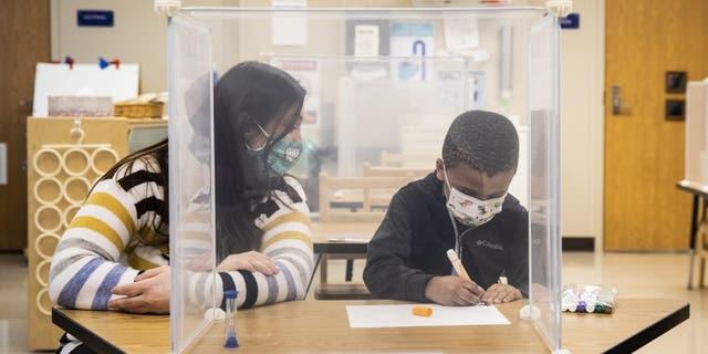 Pre-kindergarten teacher Sarah McCarthy works with a student at Dawes Elementary in Chicago, Monday, Jan. 11, 2021. (Ashlee Rezin Garcia/Chicago Sun-Times via AP, Pool)