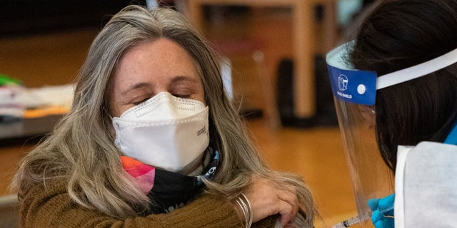 Teacher Lisa Egan is vaccinated with the Moderna coronavirus vaccine at a clinic organized by New York City's Department of Health, Monday, Jan. 11, 2021. (AP Photo/Mark Lennihan)