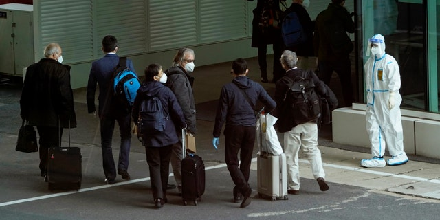 Members of the World Health Organization team arrive at the airport in Wuhan in central China's Hubei province on Thursday, Jan. 14, 2021. A global team of researchers arrived Thursday in the Chinese city where the coronavirus pandemic was first detected to conduct a politically sensitive investigation into its origins amid uncertainty about whether Beijing might try to prevent embarrassing discoveries. (AP Photo/Ng Han Guan)