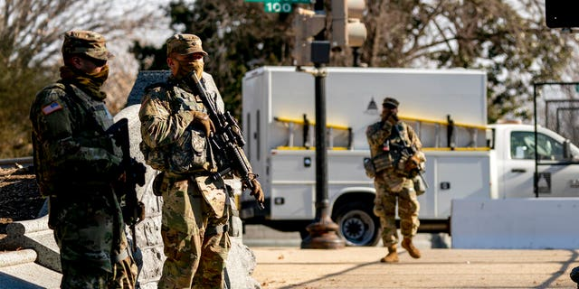 Armed members of the National Guard are stationed outside of the Capitol building on Capitol Hill in Washington, Thursday, Jan. 14, 2021. (AP Photo/Andrew Harnik)