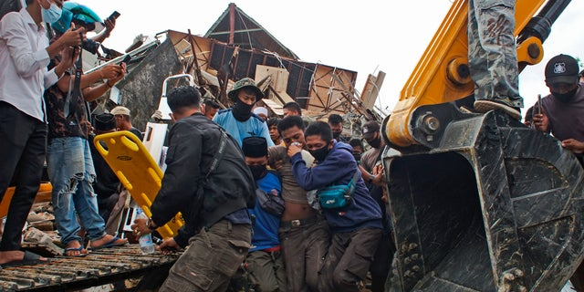 Rescuers assist a survivor pulled out from the ruin of a government building that collapsed during an earthquake in Mamuju, West Sulawesi, Indonesia, Friday, Jan. 15, 2021. (AP Photo/Azhari Surahman)