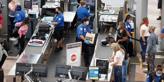 In this June 2020 file photo, TSA agents process passengers at the south security checkpoint at Denver International Airport in Denver. (AP Photo/David Zalubowski, File)
