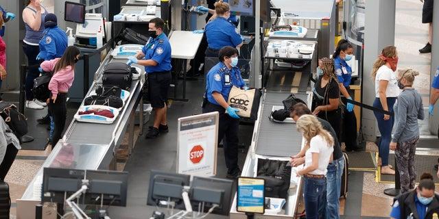 In questo giugno 2020 file di foto, TSA agents process passengers at the south security checkpoint at Denver International Airport in Denver. (AP Photo / David Zalubowski, File)