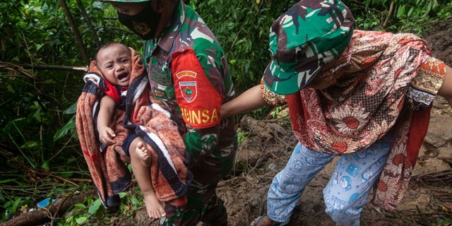 An Indonesian soldier helps a woman to carry her baby as they make their way through an area affected by earthquake-triggered landslide near Mamuju, West Sulawesi, Indonesië, Saterdag, Jan.. 16, 2021. (AP Photo/Yusuf Wahil)