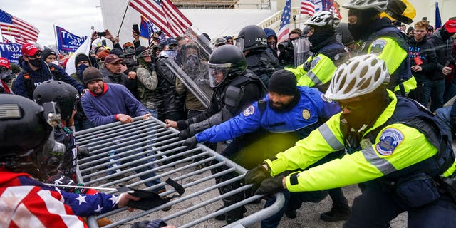 Rioters try to break through a police barrier at the Capitol in Washington. (AP Photo/John Minchillo)