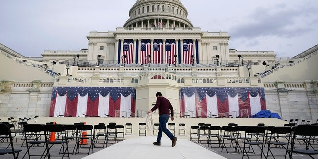 A worker pulls cables as preparations take place for President-elect Joe Biden's inauguration ceremony at the U.S. Capitol in Washington. Some school districts are electing not to live-stream the ceremony in classrooms over concerns about potential violence. (AP Photo/Patrick Semansky)