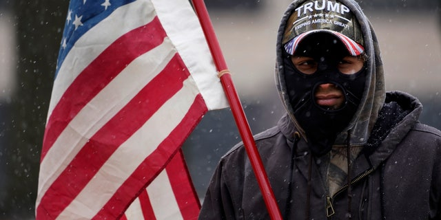 A man stands outside the state capitol wearing a Trump hat with an American flag in Lansing, Mich., Sunday, Jan. 17, 2021. (AP Photo/Paul Sancya)