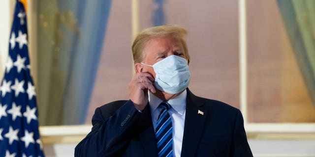 In this Oct. 5, 2020, file photo, President Donald Trump removes his mask as he stands on the Blue Room Balcony upon returning to the White House in Washington, after leaving Walter Reed National Military Medical Center, in Bethesda, Md. Trump announced he tested positive for COVID-19 on Oct. 2. (AP Photo/Alex Brandon, File)